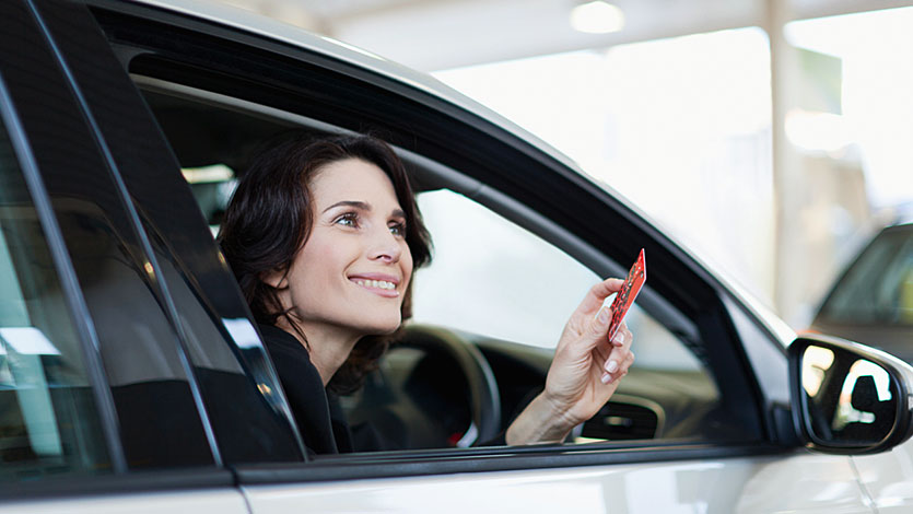 A lady holding her card, whilst looking out of the car