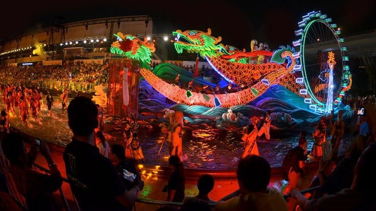 A float parading past audiences at a Chingay Parade at night